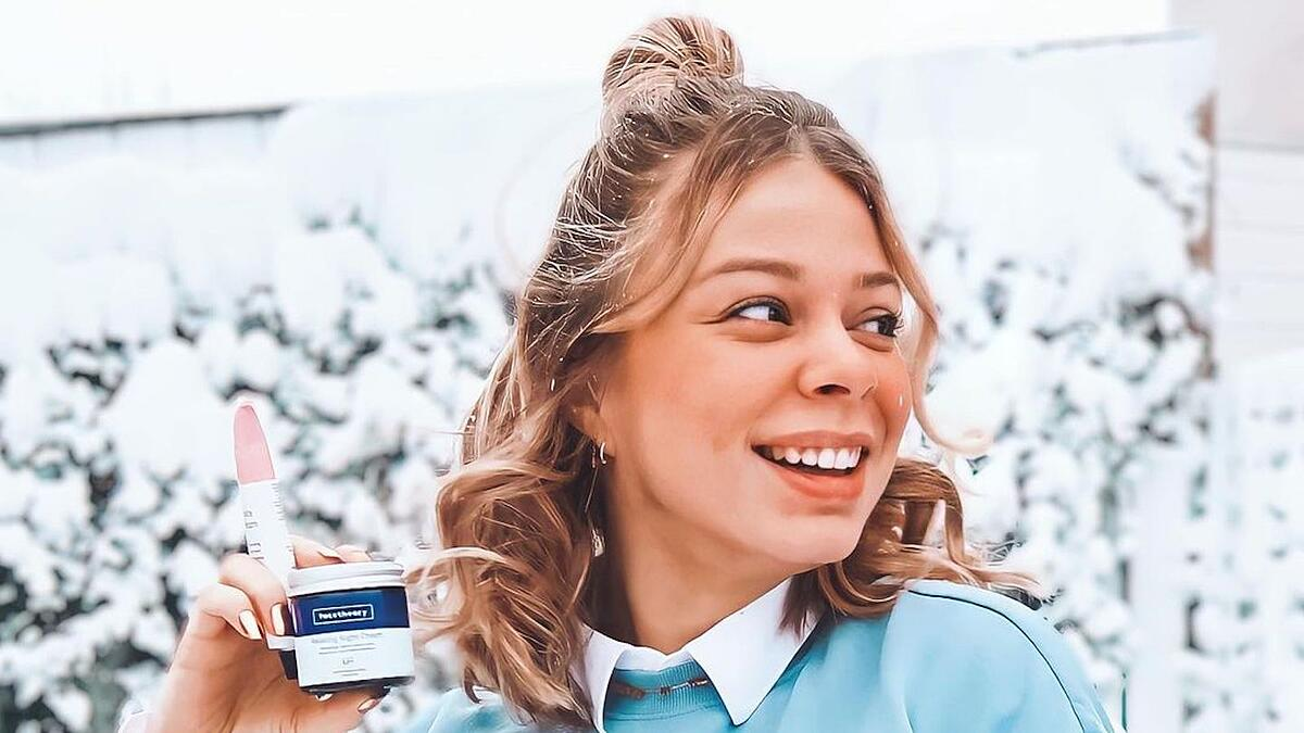 Facetheory ambassador holds 2 of their products while looking away from the camera to the right. Her hair is in a half bun and there's a snowy background behind her.