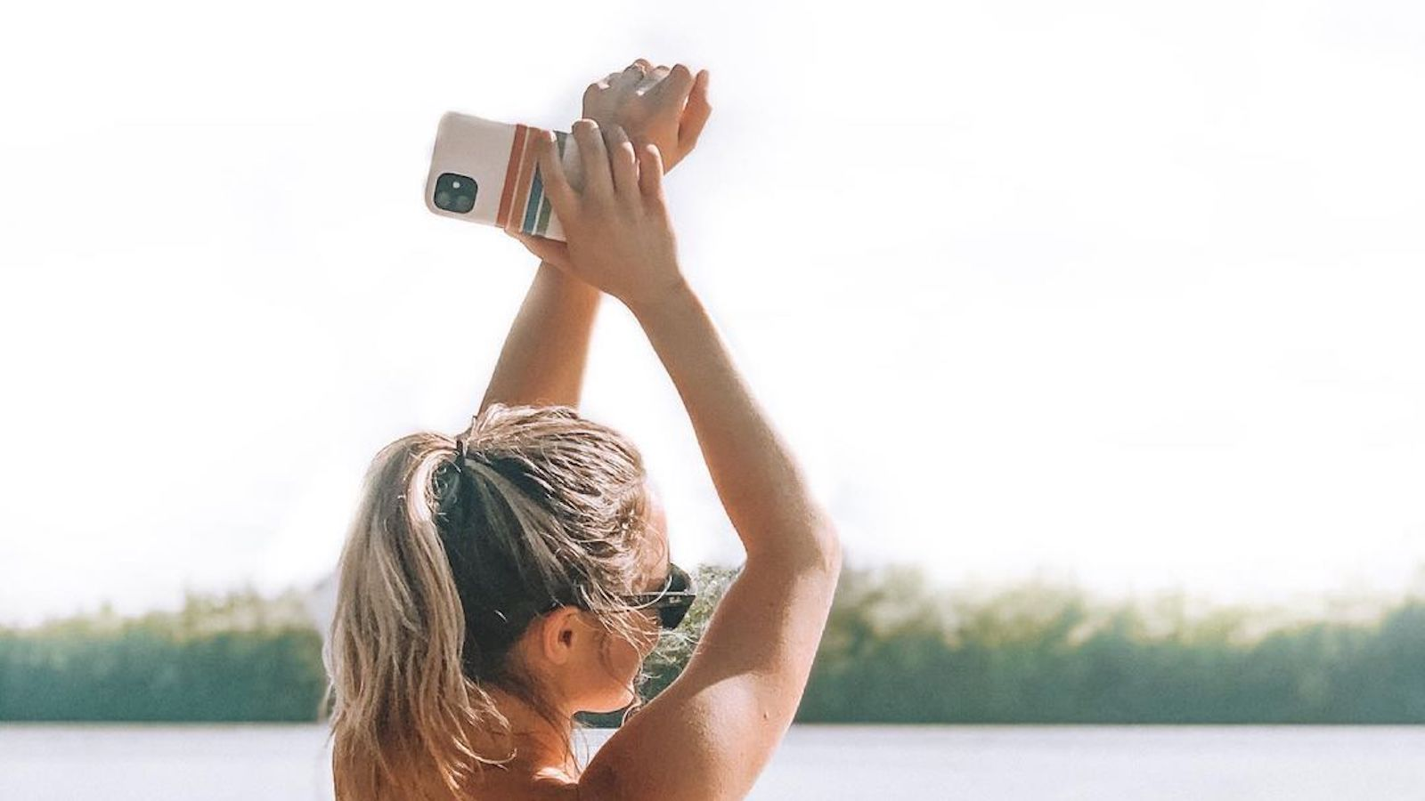 Brand ambassador @savannahwickey stand faces a lake and holds up her arms, slightly crossed. in her right hand she holds up her mobile phone with a striped Casely cover.